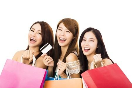 3 young Asian females shopping with retail credit card