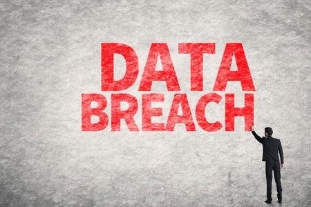 Asian business man writing Data Breach on wall