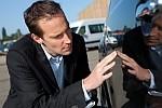 auto insurance company salesman looking at damaged car