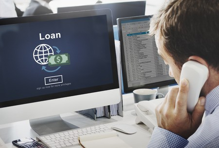 Man viewing business loan online and discussing on telephone