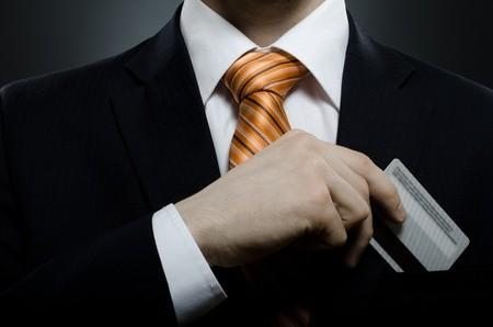 Businessman putting credit card in pocket