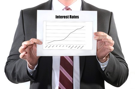 Business man holding chart showing interest rates rising