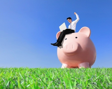 Happy businessman sitting on large piggy bank