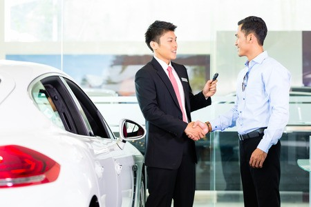 Car salesman shaking hands with buyer at dealership