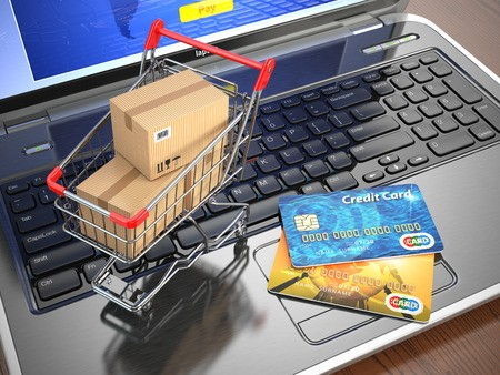 Shopping cart with boxes and credit cards on laptop
