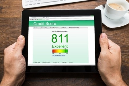 Man monitoring credit score at desk on tablet