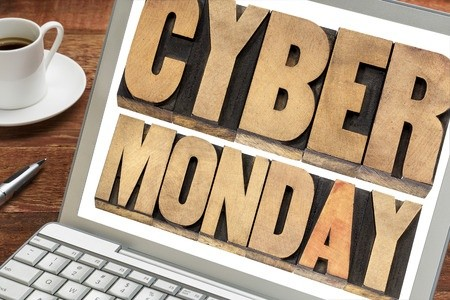 Cyber Monday spelled on laptop with coffee on desk