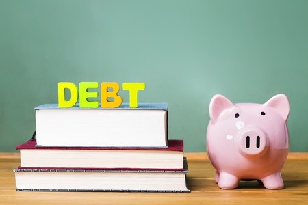 Debt, books and piggy bank atop desk with chalkboard in background