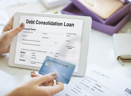 Woman holding debt consolidation loan application and credit card