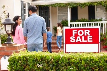 Family standing in front of home for sale yard sign