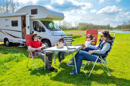 Family sitting around picnic table traveling in RV motor-home