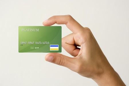 Man's hand holding green credit card up close