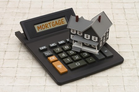 Miniature gray home atop mortgage calculator sitting on tile