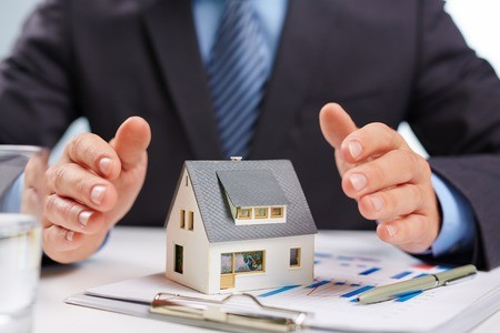 Insurance salesman with hands over miniature house