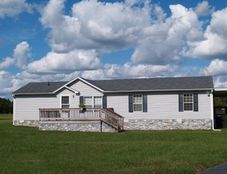 Gray manufactured mobile home with stone skirting sitting on nice grass with blue sky