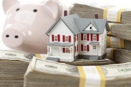 Piggy bank with small house on bundles of cash