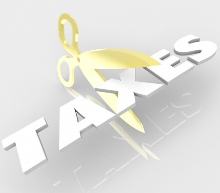 Scissors cutting the word taxes