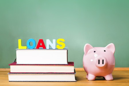 Student loans atop text books on desk with piggy bank and chalkboard