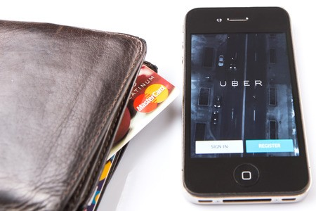 Uber smartphone App next to wallet with credit cards