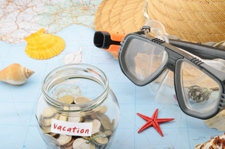 Vacation money jar on world map with shells, hat and goggles