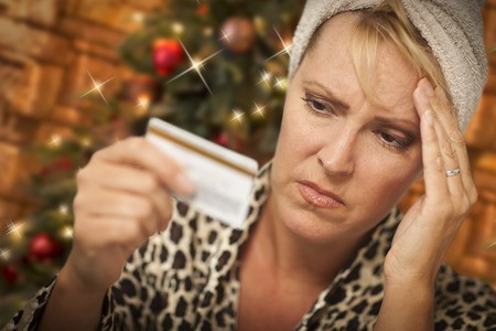Upset woman holding head and credit card with Christmas tree in background