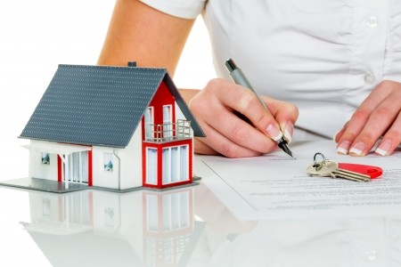 Woman signing mortgage documents to purchase a home