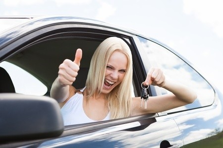 Blonde woman in car with thumbs up holding keys