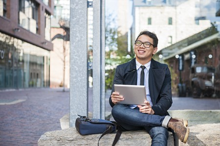 Young smiling millennial business man outside holding tablet